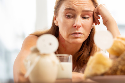 Food allergy. Close up of mature woman with facial wrinkles having food allergy to pastry and dairy