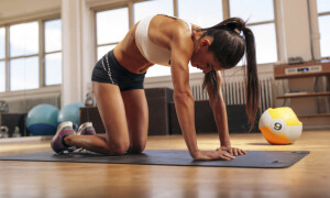 Shot of young woman stretching her back. Muscular woman exercising on fitness mat in gym.