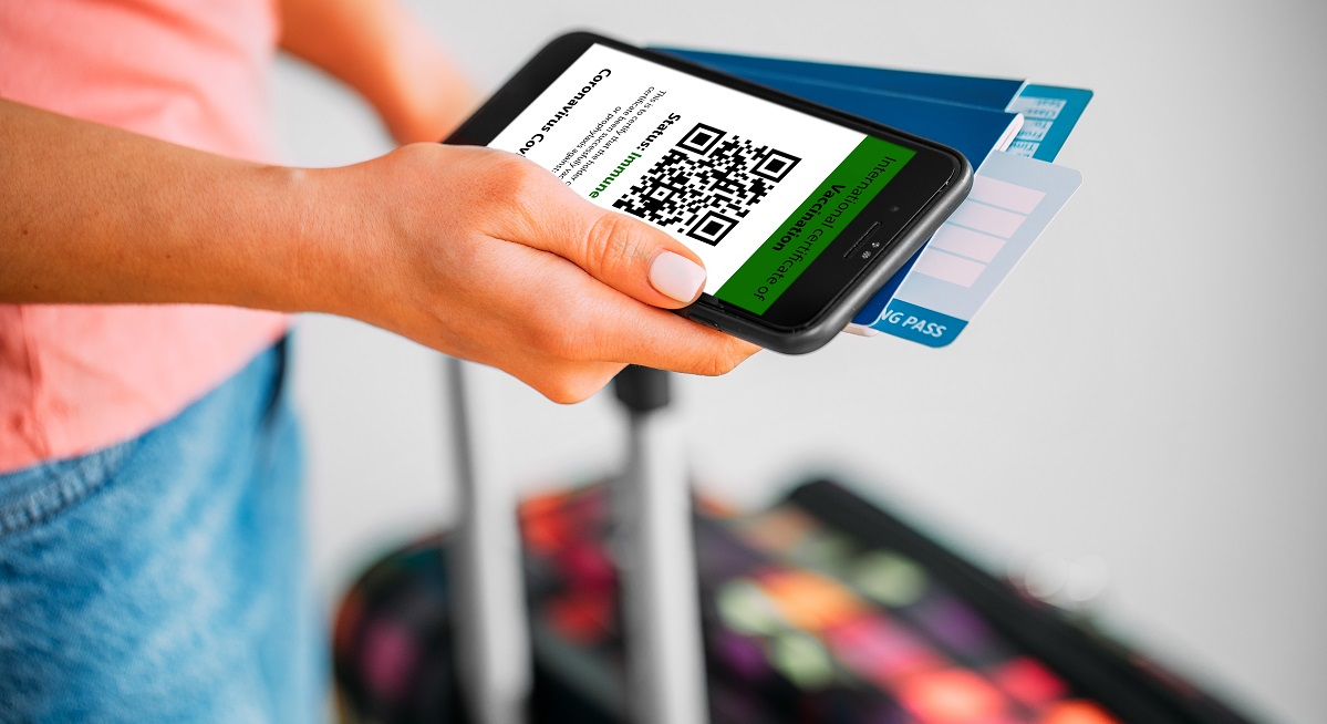 The woman holding the mobile phone a mockup for digital vaccination certificate in one hand and passport, mask and ticket in another one